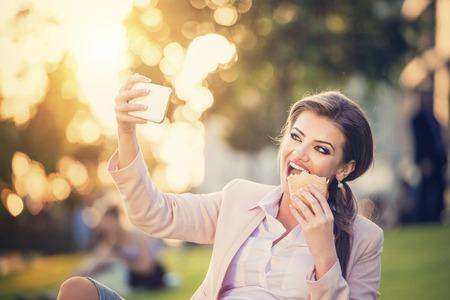 mujeres sentadas: mujer de negocios joven toma autofoto en un parque durante una pausa para el almuerzo.