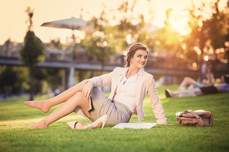 women sitting: Beautiful young business woman sitting in a park during a lunch break.