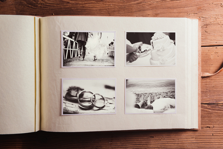 old couple walking: Wedding photos in album. Studio shot on wooden background.