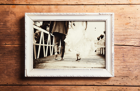 vintage photo: Picture frame with wedding photo. Studio shot on wooden background. Stock Photo