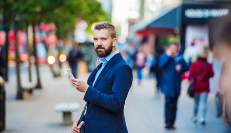 businessman phone: Handsome young manager with smartphone in London