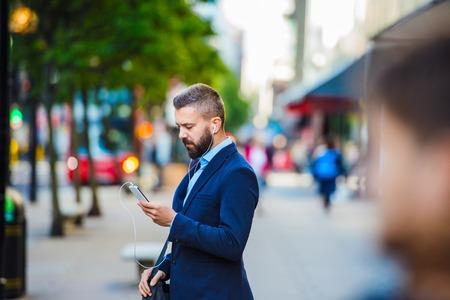 personas en la calle: Encargado joven hermoso con smartphone en Londres Foto de archivo
