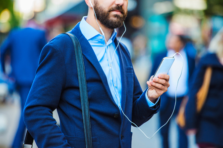 persona caminando: Encargado joven hermoso con smartphone en Londres Foto de archivo