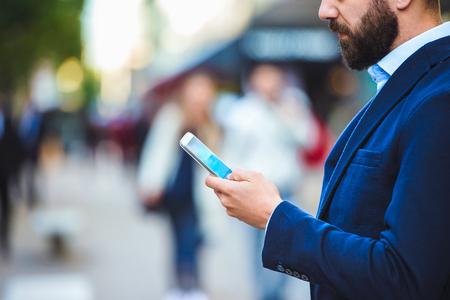 Knappe jonge manager met smartphone in Londen