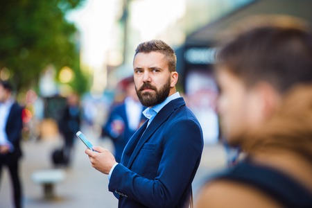 busy beard: Handsome young manager with smartphone in London
