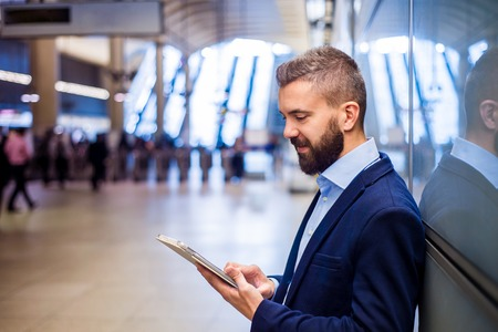 Jonge knappe zakenman met tablet in de metro Stockfoto