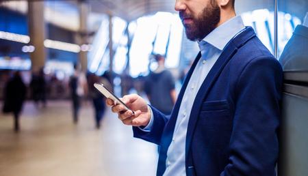 business: Junger stattlicher Geschäftsmann mit Tablette in der U-Bahn