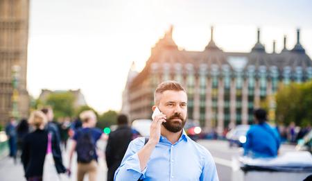 personas hablando: Apuesto joven con teléfono inteligente en el puente de Westminster
