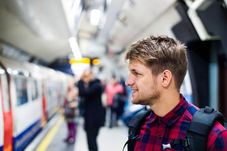 Jonge knappe mens die zich op de metro-platform Stockfoto