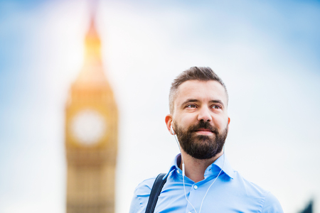 london big ben: Handsome young man in blue shirt on Westminster bridge