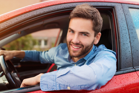 happy customer: Handsome young man in a blue shirt driving a car