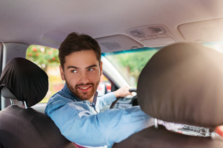 reversing: Handsome young man in a blue shirt driving a car