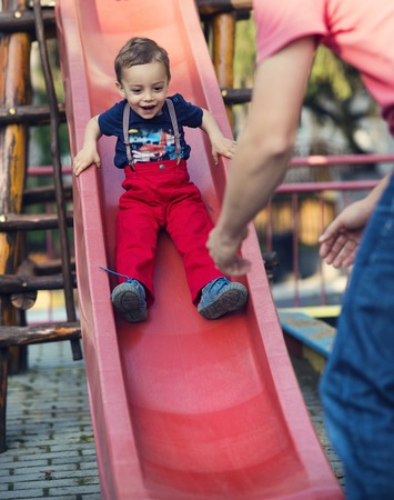 slide: Happy father playing with his son on a children playground
