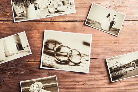 Wedding photos laid on a table. Studio shot on wooden background. Reklamní fotografie