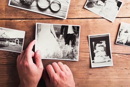 matrimonio feliz: Fotos de la boda pusieron sobre una mesa. Estudio tirado en el fondo de madera.