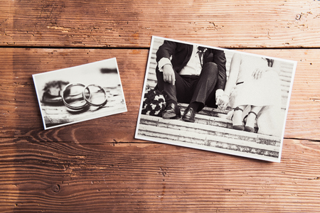 old desk: Wedding photos laid on a table. Studio shot on wooden background. Stock Photo