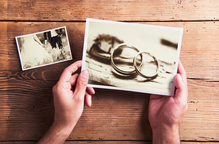 black hands: Wedding photos laid on a table. Studio shot on wooden background. Stock Photo