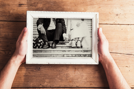 Picture frame with wedding photo. Studio shot on wooden background. Foto de archivo