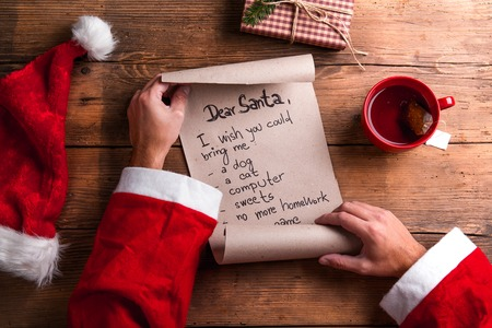 to santa: Santa Claus holding a wish list and reading it