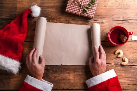 hombre con sombrero: Papá Noel que sostiene una lista de deseos vacía en sus manos