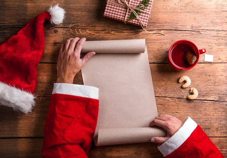 Santa Claus holding an empty wish list in his hands Stock Photo