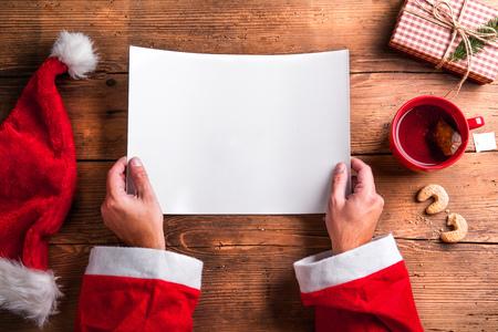 Père Noël tenant une liste de souhaits vide dans ses mains