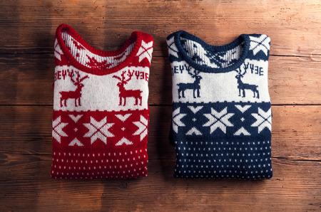 and in winter: Two winter sweaters laid on a wooden table background