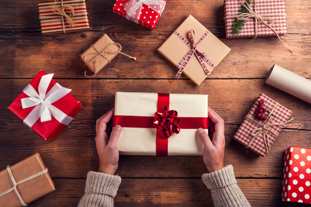 holiday backgrounds: Man holding Christmas presents laid on a wooden table background Stock Photo