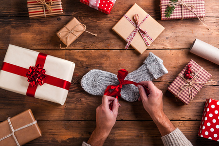 unwrapping: Man unwrapping Christmas present laid on a wooden table background