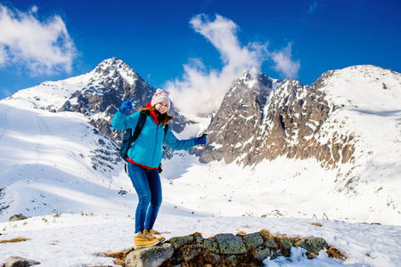 winter park: Young woman hiking outside in sunny winter mountains