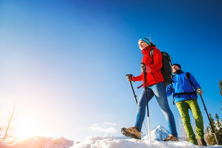couple winter: Young couple hiking outside in sunny winter mountains Stock Photo