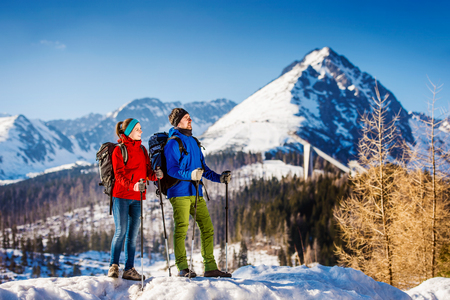 people and nature: Young couple hiking outside in sunny winter mountains Stock Photo