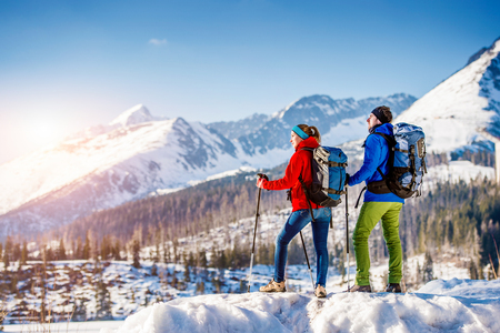 winter season: Young couple hiking outside in sunny winter mountains Stock Photo