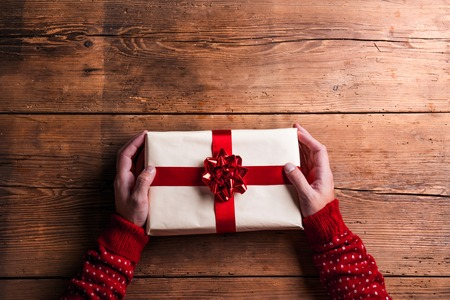 christmas gift: Man holding Christmas present laid on a wooden table background