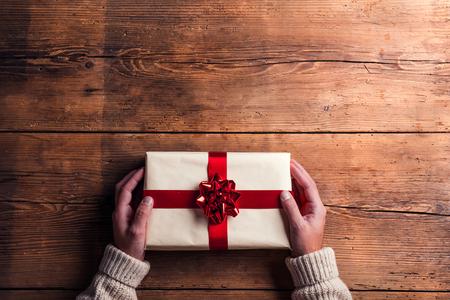 木製のテーブル背景に置かれるクリスマス プレゼントを抱きかかえた