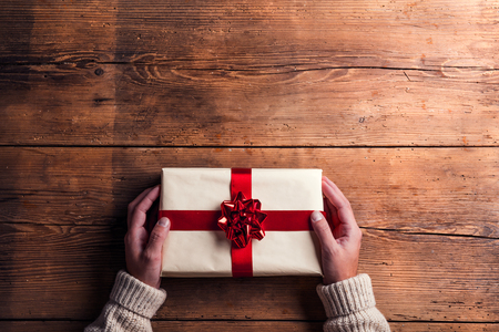 Man holding Christmas present laid on a wooden table background