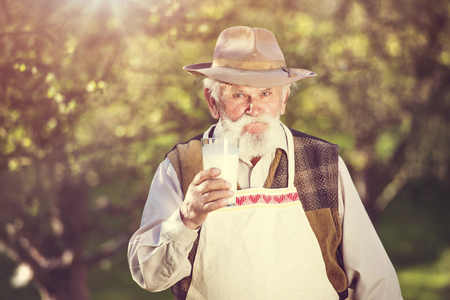 milk mustache: Senior man in orchard with glass of milk