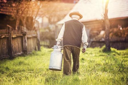 Senior man met een melkketel op zijn boerderij Stockfoto