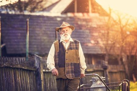 outside house: Senior man carrying a milk kettle on his farm