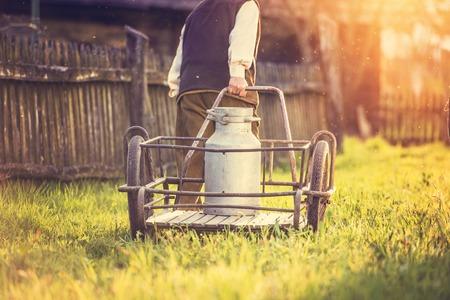 old farmer: Senior man carrying a milk kettle on his farm