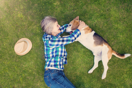 pet therapy: Beautiful senior woman with her dog lying on grass Stock Photo