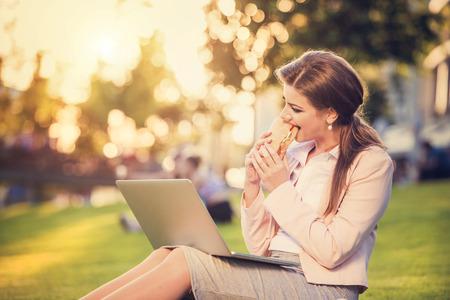 pause repas: Belle jeune femme d'affaires assis dans un parc au cours d'une pause d�jeuner. Banque d'images