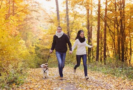 Belle jeune couple avec un chien dans la forêt d'automne