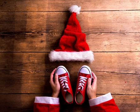 red shoes: Christmas composition. Studio shot on wooden background. Stock Photo