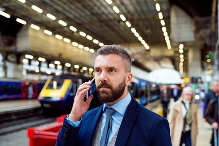 train: Young handsome businessman with smart phone in subway