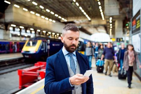 Jonge knappe zakenman met slimme telefoon in de metro Stockfoto