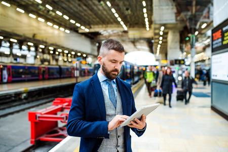 hombre de negocios: Apuesto hombre de negocios joven con la tablilla en el metro