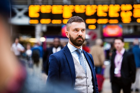 buss: Young handsome businessman standing at the crowded station Stock Photo