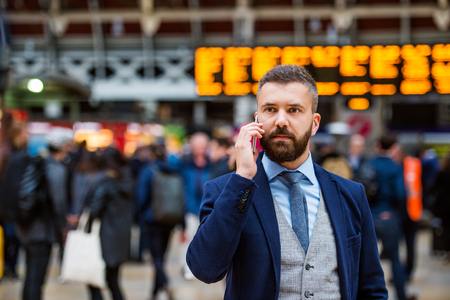 people   lifestyle: Young handsome businessman with smart phone standing at the crowded station