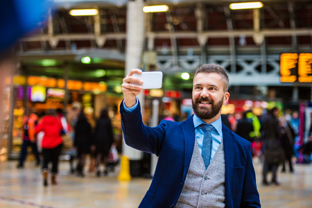 buss: Young handsome businessman with smart phone standing at the crowded station